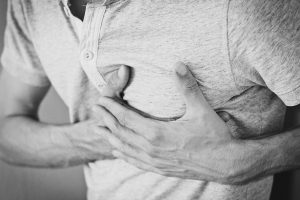 black and white picture of a mans torso with his hands holding his heart area.