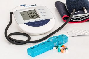 blood pressure machine with a weekly pack of pills in front of it