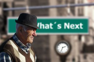 """older caucasian man with a green sign behind him that says """"what's next"""""""