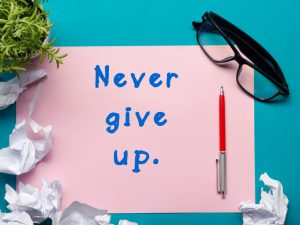 never give up on a pink piece of paper and a red pen next to the words.