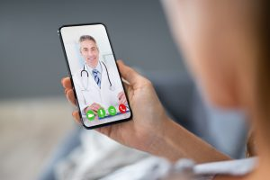 person holding a cell phone with a caucasian male doctor on the screen