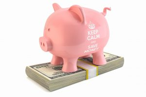 pink piggy bank standing on top of some money