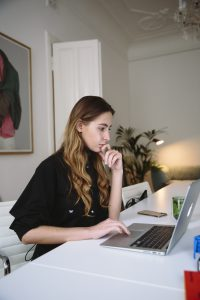 caucasian woman sitting at a desk looking at her laptop with her hand on her chin