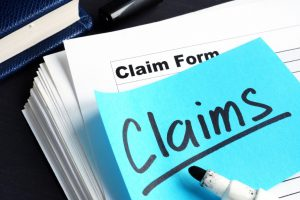 "claims written on a blue post it note that is on top of a stack of paperwork with the word ""claim form"" on the top"