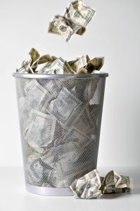 hundred dollar bills and other bills crumbled in a trash can