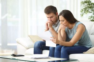 caucasian man and woman sitting on a couch looking worried with a piece of paper in the womans hand