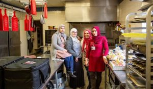 women in hijabs standing next to each other in a kitchen, with one woman sitting on the table smiling.