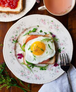 dish with an egg on toast and a cup of tea next to it on the table