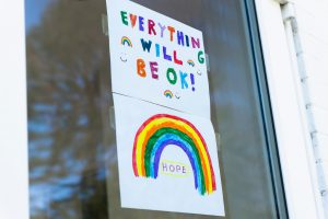 everything will be okay written on a poster with a rainbow on the bottom that is taped to a window