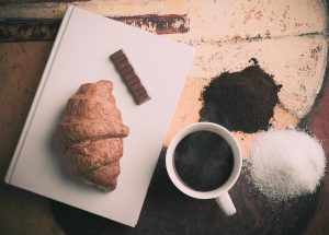 cup of black coffee with a croissant and piece of chocolate on a plate next to the cup