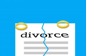 two rings on the ends of a paper with the word divorce on the paper and a rip in the middle