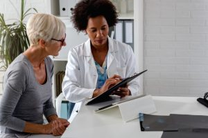african american woman with a white labcoat on showing a caucasian woman something on her clipboard
