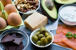 eggs, olives, salmon, avocado, cheese, and dark chocolate on a table