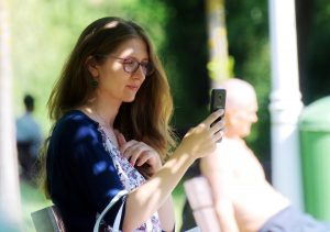 caucasian woman sitting outside with her phone up to her face looking at it with a smile