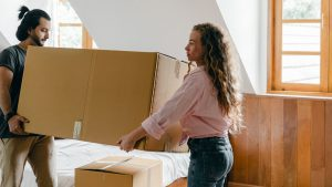 man and woman moving a heavy cardboard box together