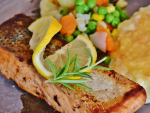 salmon cooked with a slice of lemon on it and vegetable medley next to it on the plate.