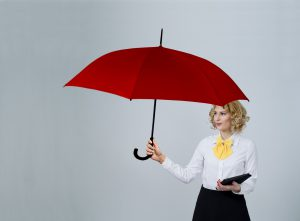 caucasian woman in business attire holding a red umbrella