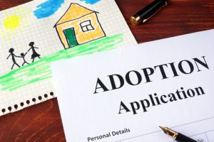 adoption application with another paper with a drawing of a house and parents holding a kids hand