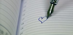 opened notebook with a pen writing a little heart in the middle of the page.