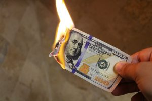 a hundred dollar bill on fire, burning.