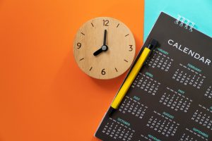 a clock with a black calendar next to it with an orange background