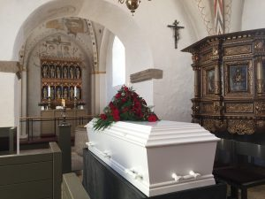 white casket in a church with red roses placed over it