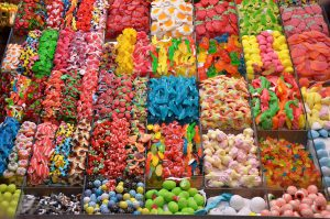 an assortment of different kinds of candies in bins