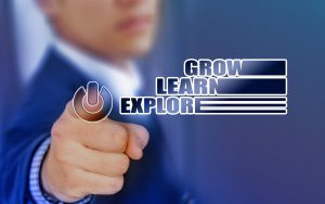 """person in  a suit pressing a button with the words """"grow, learn, explore"""" next to it"""