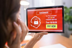 a woman holding up a tablet with a red screen and the word ransomware on it