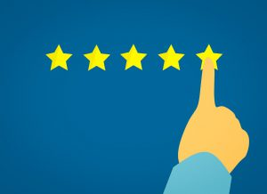 hand with the pointer finger pressing on the 5th star of a review.