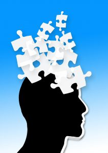 silhouette of a head in black with white puzzle pieces coming out of it