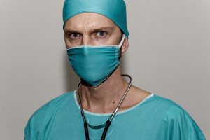 caucasian man that appears to look mad with teal scrubs on, mask and hat, as well as a stethoscope around his neck.