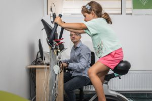 caucasian little girl on a stationary bike with wires connected and a man sitting down in the background watching
