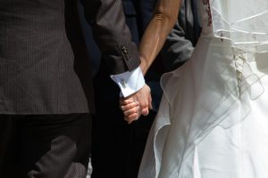 two hands holding each other, one of a man in a suit and the other a woman's in a wedding gown