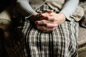 caucasian hands holding each other on a woman's lap with a skirt and cardigan on
