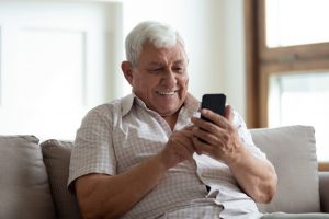 older caucasian man sitting on his couch holding a cell phone up smiling