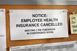 "notice on a board that says ""employee health insurance cancelled, meeting at 1 pm tomorrow"""