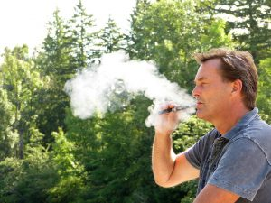 caucasian man smoking a vape pen with a lot of smoke coming out of it.