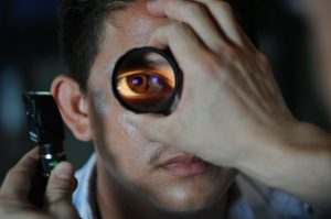 man with a magnified glass in front of his eye