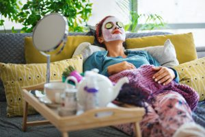 woman laying on her couch with a face mask and tea on a table.