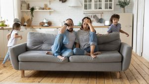 man and woman sitting on a couch with their hands on their hand while two kids run around the couch in a circle