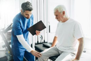 older man sitting on a table with a male doctor touching his knee with one hand and holding a clipboard in another.