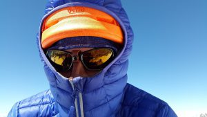 person in a blue coat with sunglasses on and orange hat with blue hoodie up