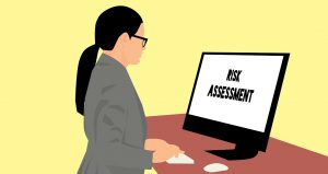 "illustration of a woman in business attire looking at a computer screen that says ""risk assessment"" on it"