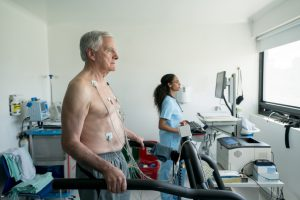 older caucasian man on a treadmill with no shirt on and wires stuck to his chest with a doctor in the background