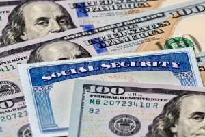social security card with hundred dollar bills surrounding it