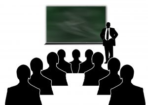 silhouettes of a person in a suit in front of a board with people sitting down in front of him