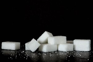 black background with white sugar cubes on a black table.