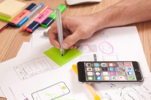 person's hand writing down on post it note with cell phone close by and a drawing of phone on paper with other writing surrounding it