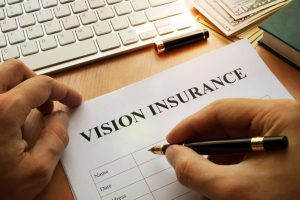 vision insurance on a paper with a hand with a pen in it about to fill it out